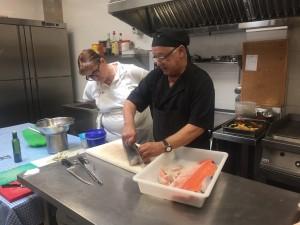 La Carme Rodríguez, participant del curs d'auxiliar de cuina, seguint atentament els trucs que li ensenya Eugeni Piñol, el cuiner de l'Hotal la Creu, on ha fet les seves pràctiques.